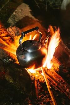 Faire bouillir de l'eau en utilisant kettle sur un feu de joie dans le village d'akha
