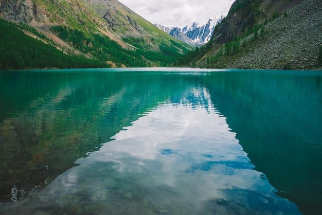Faire briller l'eau dans le lac de montagne dans les hautes terres. magnifiques montagnes enneigées géantes. le ruisseau coule du glacier. blanche neige claire sur la crête. incroyable paysage atmosphérique de nature majestueuse.