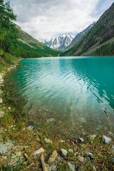 Faire briller l'eau dans le lac de montagne dans les hautes terres. magnifiques montagnes enneigées géantes. le ruisseau coule du glacier. blanche neige claire sur la crête. magnifique paysage atmosphérique de la nature majestueuse de l'altaï.