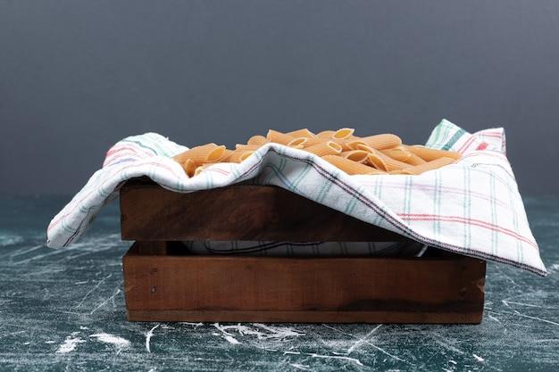 Faire brunir les pâtes penne crues dans un panier en bois. photo de haute qualité