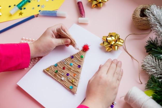 Faire la carte de noël à la main.concept de bricolage pour enfants. faire une décoration de jouets de noël ou une carte de voeux