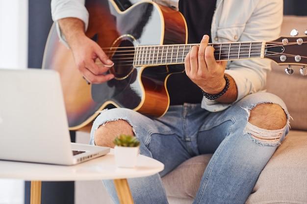 Faire une chanson. l'homme en vêtements décontractés et avec guitare acoustique est à l'intérieur.