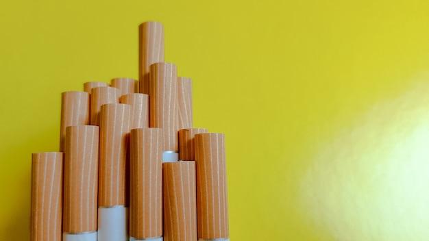 Faire une cigarette. photo de filtres jaunes de cigarettes sur fond jaune. lumière naturelle.