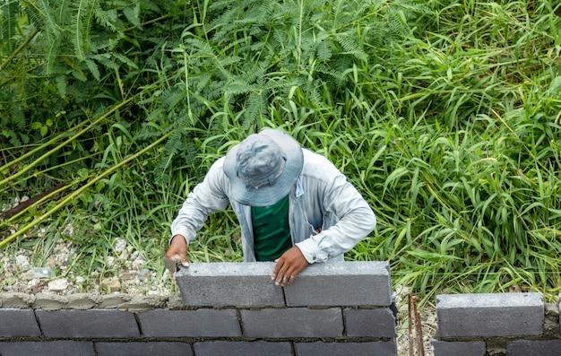 Faire une clôture en briques pour une maison de sécurité avec la force de l'homme