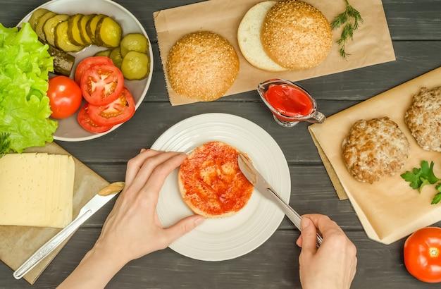 Faire cuire un hamburger étape par étape, étape 3 - étaler le pain avec la sauce tomate