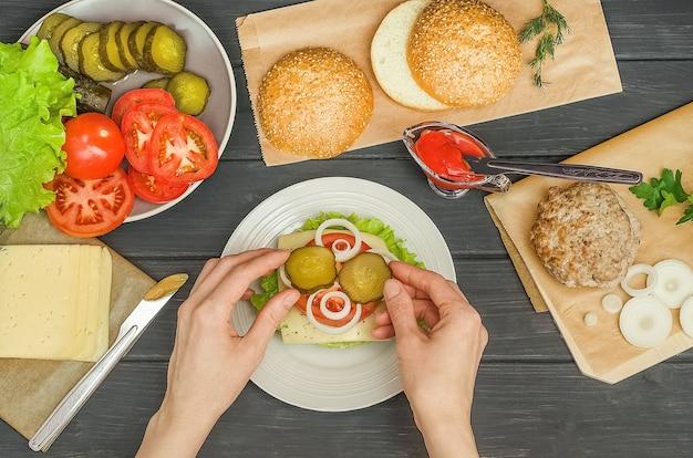 Faire cuire un hamburger étape par étape, étape 8 - mettre l'oignon et le concombre mariné sur la tomate