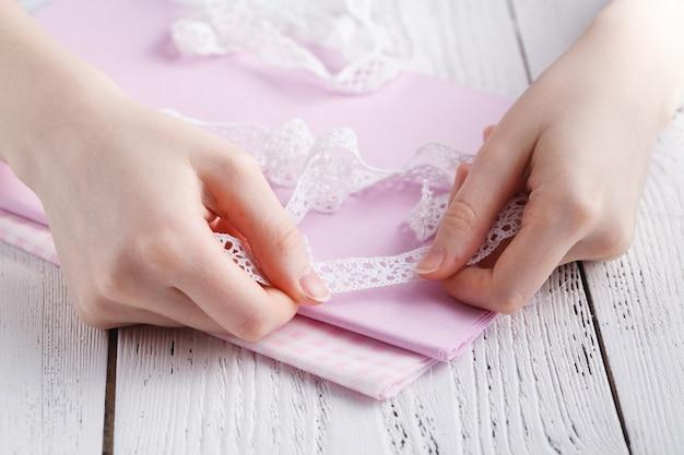 Faire des décorations de table. une photo de femme cousant une nappe en lin beige naturel, des serviettes et des serviettes avec un imprimé rose et une bordure en dentelle de lin blanc au crochet, à l'aide d'aiguilles
