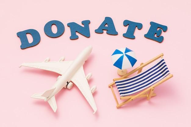 Faire un don de mot jouet avion parasol et chaise longue sur fond rose concept sur le thème du don de vacances