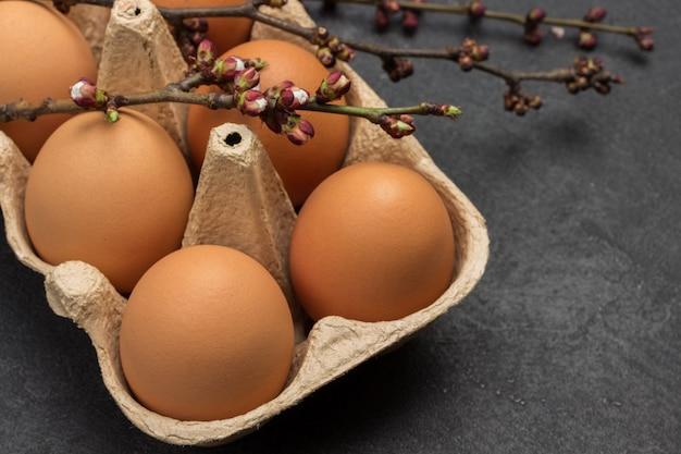 Faire dorer les œufs de poule dans un contenant en carton. brindilles avec boutons floraux. surface noire. fermer. vue de dessus