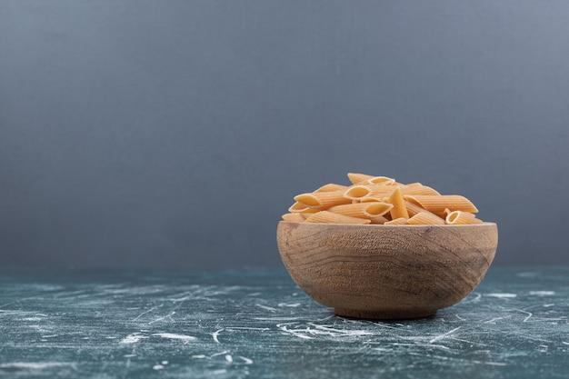 Faire dorer les pâtes penne crues dans un bol en bois. photo de haute qualité