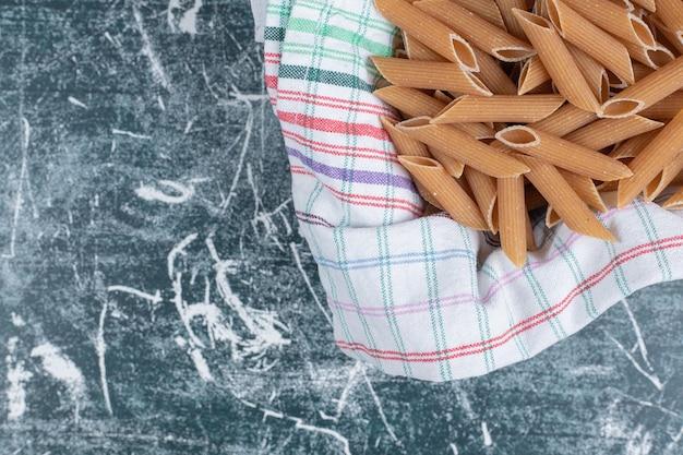 Faire dorer les pâtes penne crues sur une nappe à rayures. photo de haute qualité