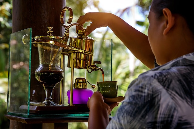 Faire du café légendaire, kopi luwak, dans un siphon vintage.