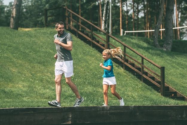Faire du jogging avec le père. toute la longueur du joyeux père et fille faisant du jogging ensemble dans le parc