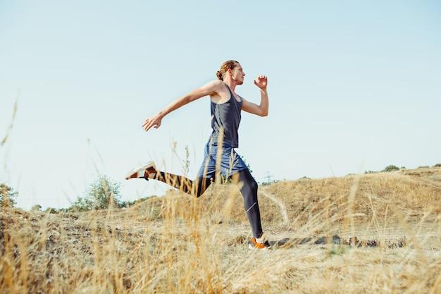 Faire du sport. coureur d'homme sprintant en plein air dans une nature pittoresque. monter la piste d'entraînement d'athlète masculin musclé en cours d'exécution pour le marathon.