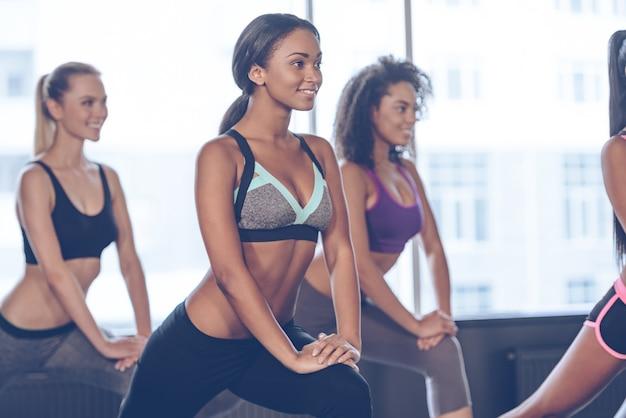 Faire du sport dans la joie. gros plan de belles jeunes femmes avec des corps parfaits en vêtements de sport faisant de l'exercice avec le sourire en se tenant devant la fenêtre de la salle de sport