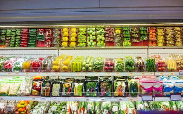 Faire des emplettes dans le supermarché pour la santé un légume et le fruit d'étagère d'achat mis sur eux à la nourriture dans le supermarché