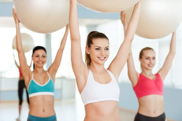 Faire de l'exercice avec des ballons de fitness. trois belles jeunes femmes en vêtements de sport
