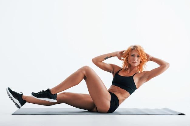 Faire de l'exercice. bodybuilder femme rousse est en studio sur un espace blanc.