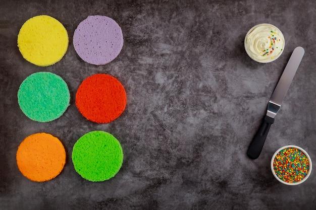 Faire un gâteau arc-en-ciel fait maison avec de la crème blanche et une spatule.