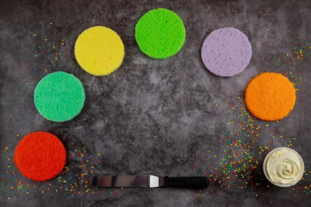 Faire un gâteau en couches arc-en-ciel avec de la crème blanche et une spatule.