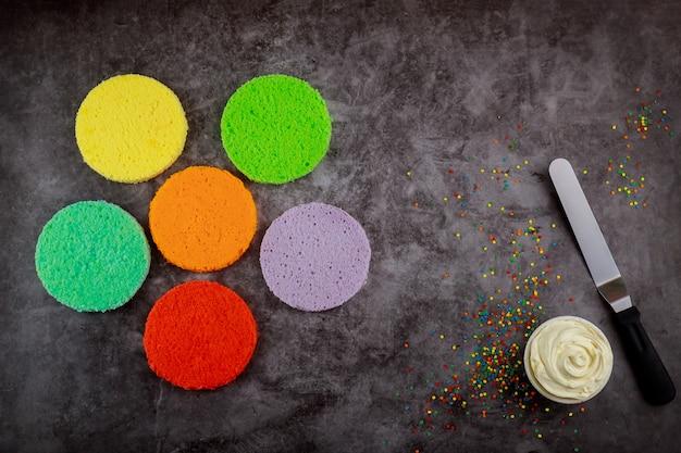 Faire un gâteau en couches arc-en-ciel avec de la crème blanche.