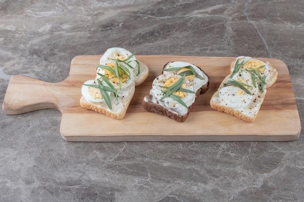 Faire griller du pain avec des œufs durs sur une planche de bois.