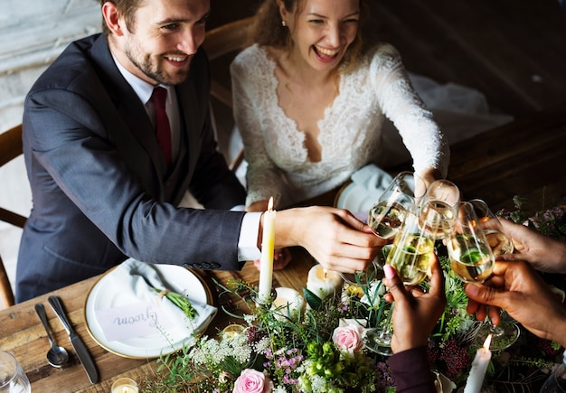 Faire griller les jeunes mariés avec des verres à vin lors d'une réception de mariage