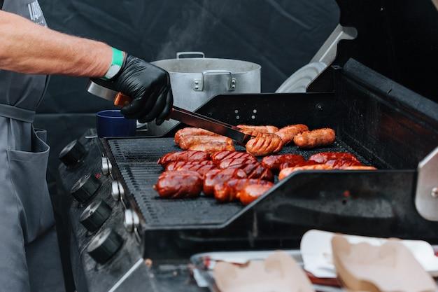 Faire griller des saucisses sur le gril du barbecue. barbecue dans le jardin. festival de cuisine de rue