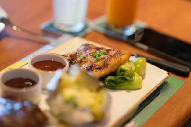 Faire griller un steak de poulet avec une pomme de terre au four flou avec une sauce