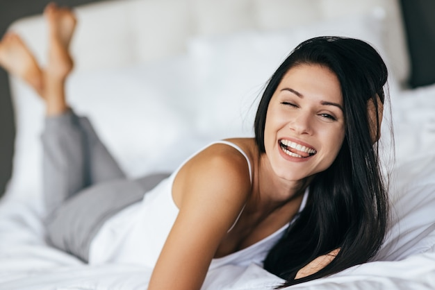 Faire une grimace. jeune femme faisant une grimace et souriant en position couchée sur le lit à la maison