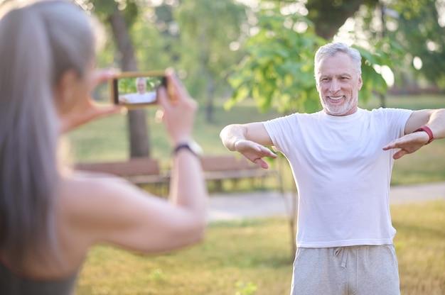Faire des images. une femme fait une photo de son mari pendant qu'il fait de l'exercice