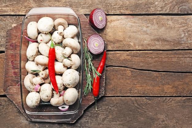 Faire mariner les champignons avec des épices sur une table en bois