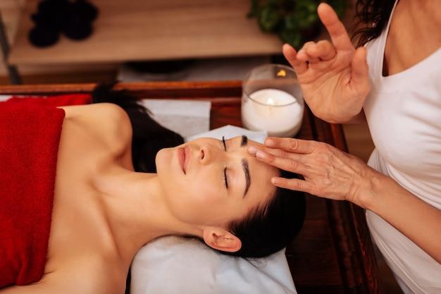Faire un massage du visage. femme experte exotique en uniforme blanc étant masseuse inhabituelle dans un salon spa professionnel
