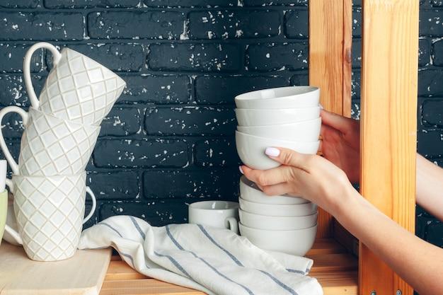 Faire le ménage dans une cuisine, une femme et de la vaisselle