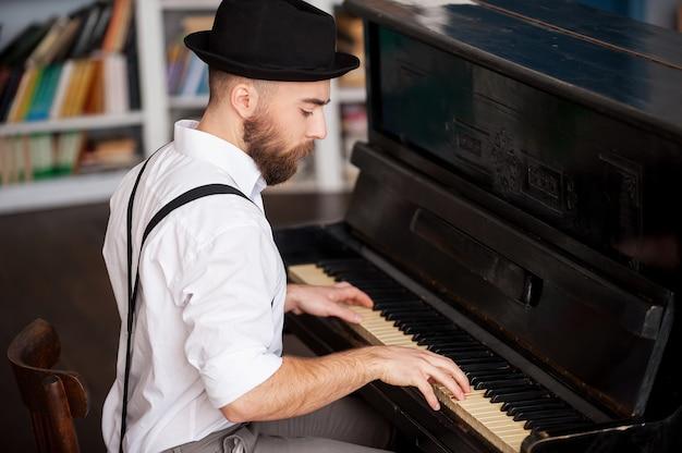 Faire de la musique. profil d'un beau jeune barbu jouant du piano