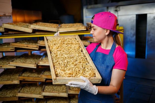 Faire les nouilles. fabrique de pâtes. fabrication de spaghettis. pâtes crues. travailleur avec une boîte de pâtes. fille travaille dans la production de pâtes