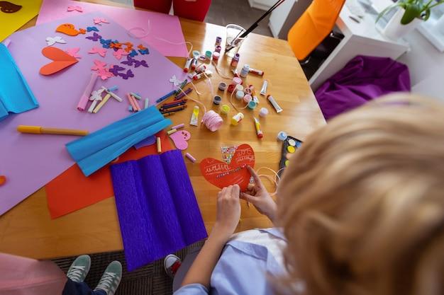 Faire ornement appliqué. vue de dessus d'un écolier blond faisant des ornements appliqués à la leçon