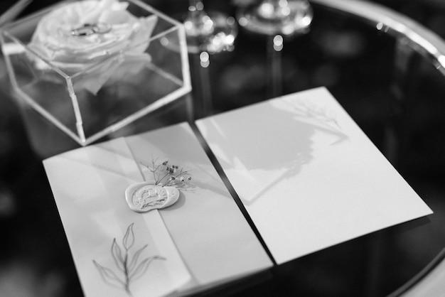 Faire-part de mariage dans une enveloppe bleue sur une table avec des brins verts
