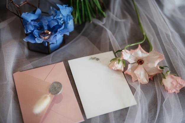 Faire-part de mariage dans une enveloppe grise sur une table avec des brins verts