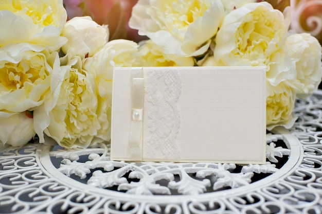 Faire-part de mariage festif dans un style doux sur fond de fleurs.