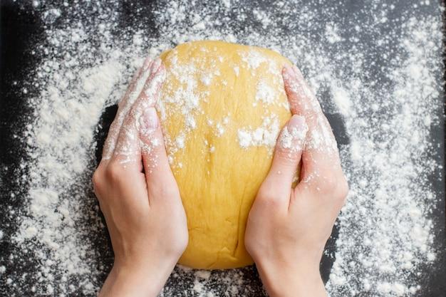 Faire de la pâte par des mains féminines sur fond noir