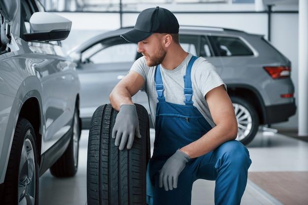 Faire une pause. mécanicien tenant un pneu au garage de réparation. remplacement des pneus hiver et été.