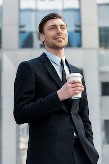 Faire une pause. portrait d'un jeune homme d'affaires buvant du café du matin à l'extérieur