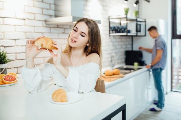 Faire le petit déjeuner dans la cuisine, jolie femme blonde souriante tenant un croissant, des aliments sains assis sur une chaise.