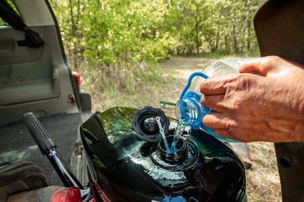 Faire le plein à partir d'une bouteille en plastique d'un gros plan de réservoir de bateau.