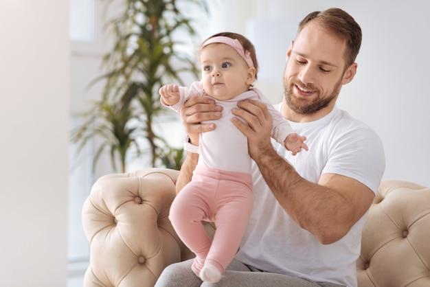 Faire les premiers pas. heureux homme impliqué prudent assis sur le canapé à la maison et étreignant son enfant tout en exprimant des émotions tendres et au repos