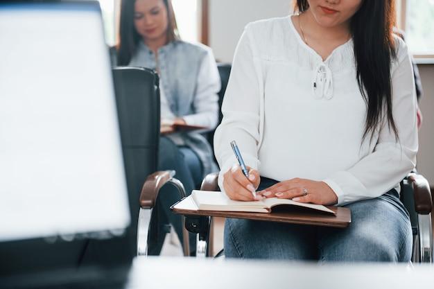 Faire quelques notes. groupe de personnes lors d'une conférence d'affaires dans une salle de classe moderne pendant la journée