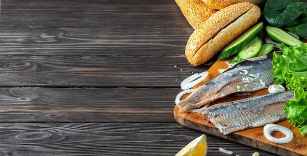 Faire un sandwich au filet de hareng avec des oignons, du concombre et de la salade sur une planche de bois