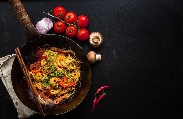 Faire sauter les nouilles dans un wok chinois traditionnel, des baguettes, des ingrédients. espace pour le texte. nouilles asiatiques aux légumes, crevettes.