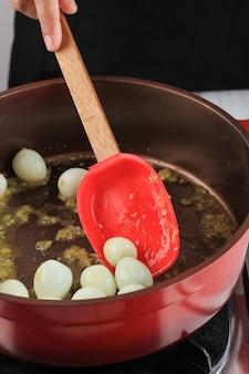 Faire sauter l'oeuf de caille bouilli sur une poêle rouge avec une spatule rouge. processus de cuisson dans le menu cuisine faire des œufs de caille